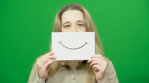Mladá dívka pózuje. Veselý smajlík na kousek papíru. Vyvolá řizuje jeden. Zelené pozadí. Pokrytectví