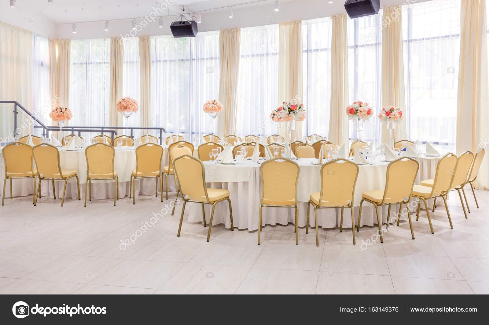 Schön eingerichtetes Zimmer mit gedeckte Tische mit Blumen im ...