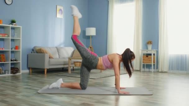 Junge Frau trainiert in Wohnung