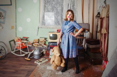 portrait of beautiful blonde woman with old teddy bear in soviet union interiour