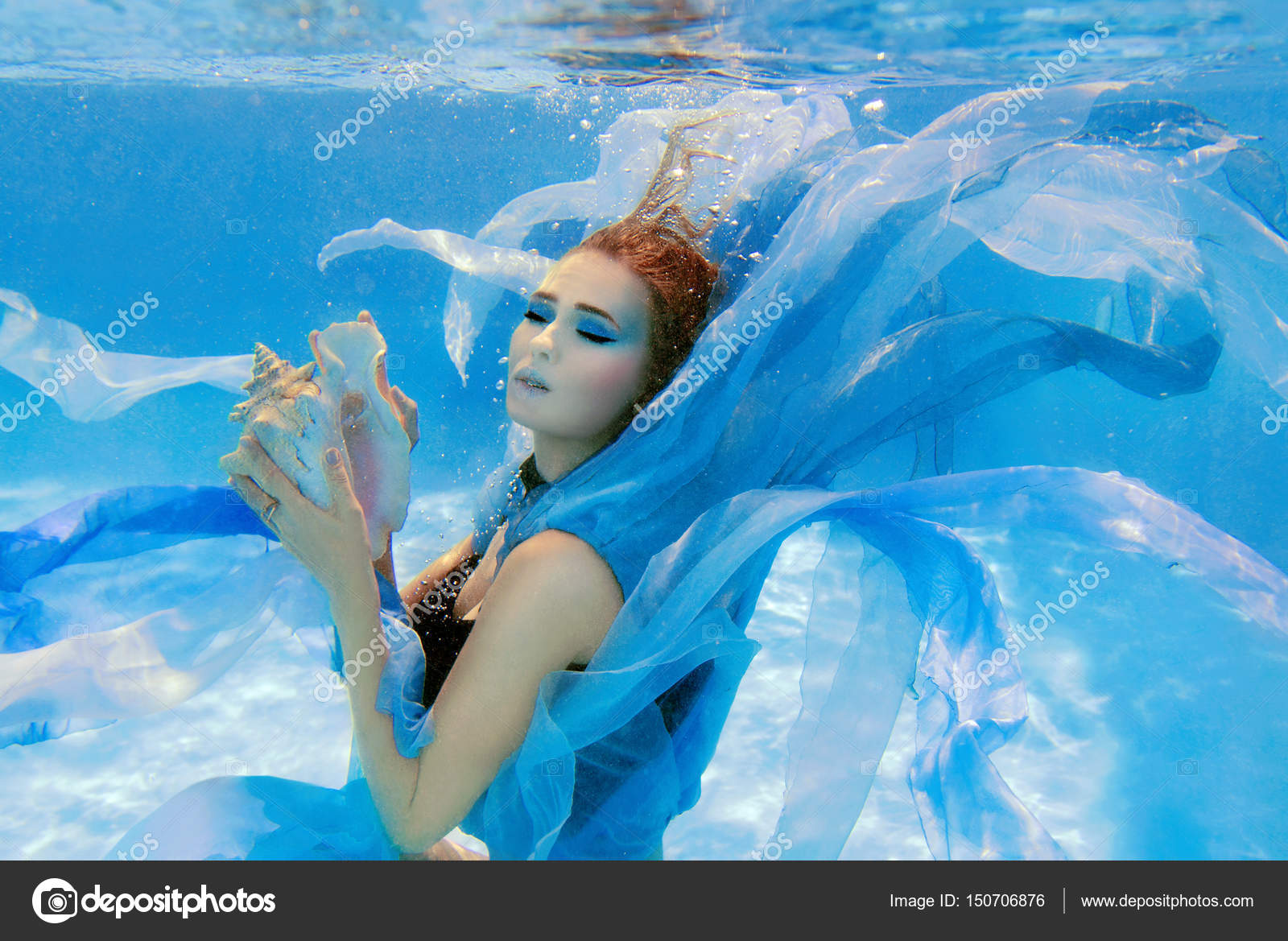 Underwater fashion portrait of beautiful young woman in blue