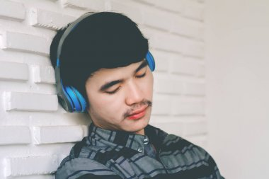 Young hipster gay man listening music headphones.