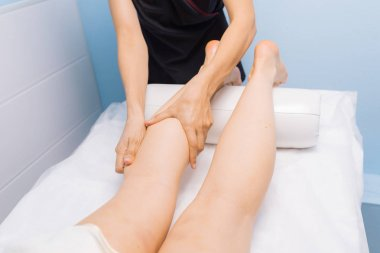 The specialist does massage of the knees to the client of the ma