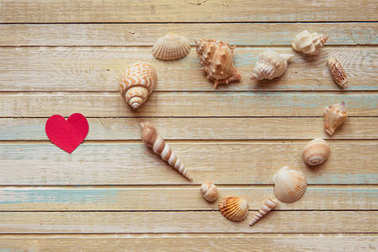 Seashells shaped heart on a wooden background top view