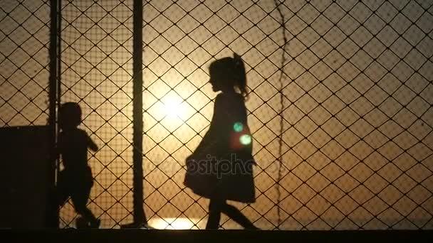 bambini piccoli che correvano il trampolino su uno sfondo di tramonto del mare