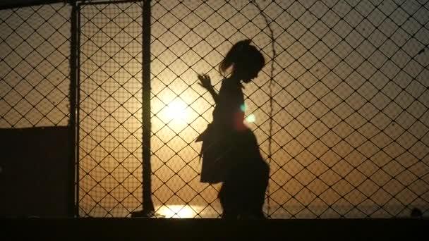 bambini che saltano sul trampolino su uno sfondo di tramonto delloceano