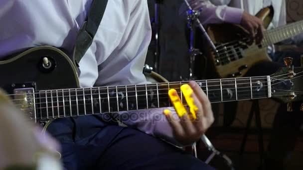 člověk hraje na elektrickou kytaru v jazzový orchestr
