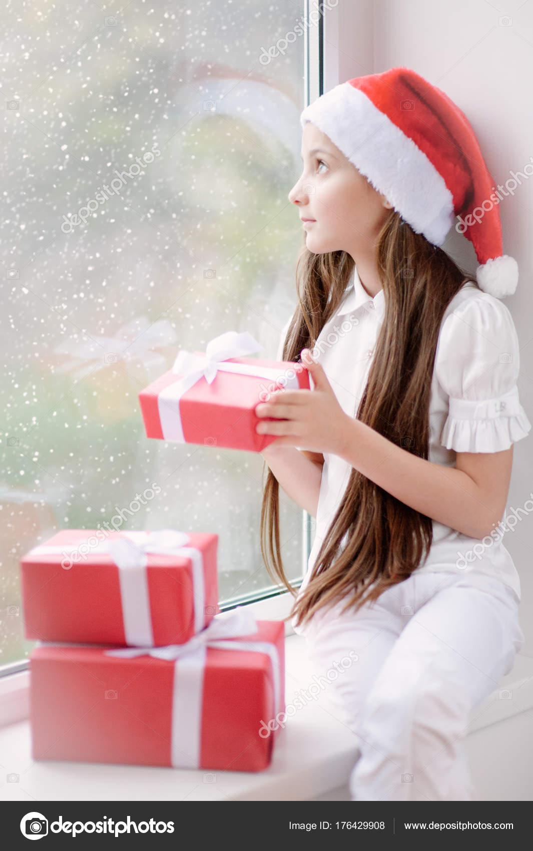 71a78f51d7e27 Beautiful little girl in Santa hat dreaming by the window with snow behind  holding a box with gift in Christmas Eve — Photo by photo zaur.mail.ru