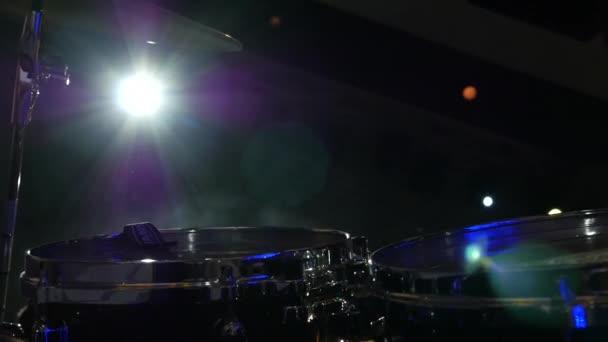 élő rock zenekara, a dobos kezet játszik a színpadon a sugarak a fény koncert