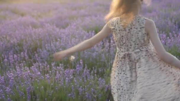roztomilá holčička vesele tančí s úsměvem na tváři venku v nádherné levandulové pole v teplé letní večery