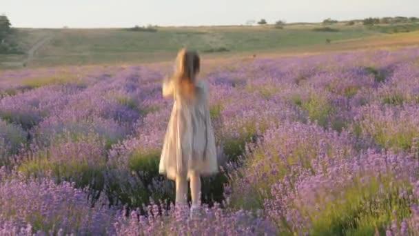 roztomilá holčička vesele utíká a šťastně skákání venku v nádherné levandulové pole v krajině provence