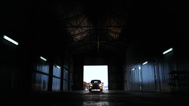 car silhouette headlight glow front view. automobile arrive service station. large garage. machine drives into for diagnosis
