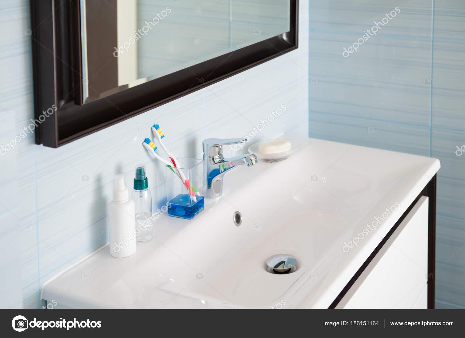 Bagno bianco blu luminoso con lavabo con miscelatore spazzolino da