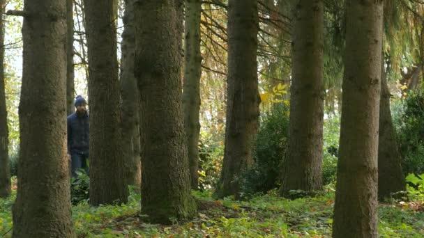 atraktivní muž chodí se psem. být v patách kráčení podzim v parku. majitel psů pohlazení. Francouzský buldoček. cestování s domácími zvířaty venku v lese