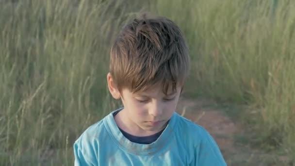 portrétní chlapeček ze slumů sklopil rozmrzele hlavu a postavil se na pole. smutné dítě venku ztratil rodinný dům byl zničen válkou.