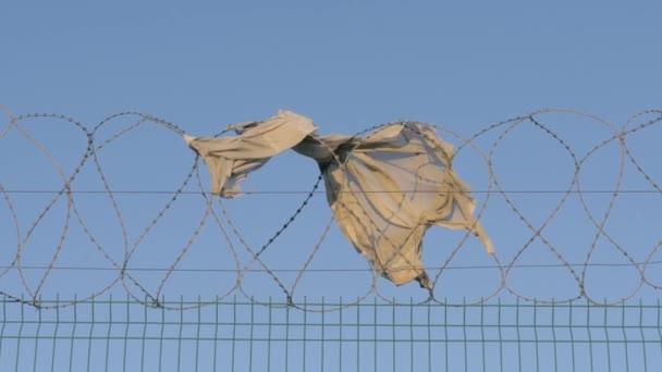 koncepce uniknout zachraňování životů, porušení zákona zahrnuje trestní sankce. zblízka kus oblečení visí ostnatý drát plot v chráněné oblasti.