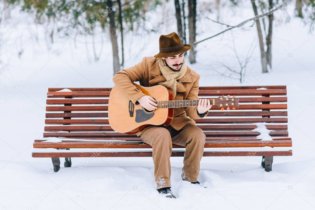 guy playing guitar in park in winter