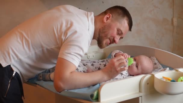 Dad plays with a small child. Father gives his newborn son a foot massage with a rubber ball