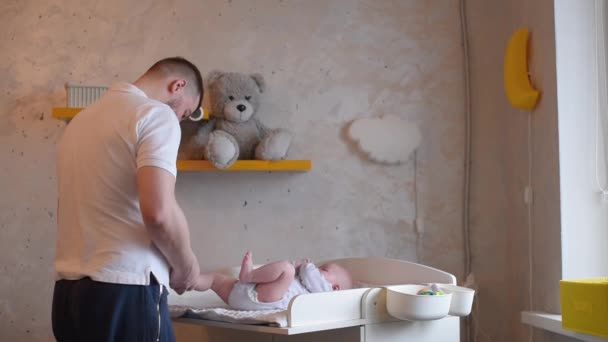 A father is dressing his little child. Dad caring for a newborn baby