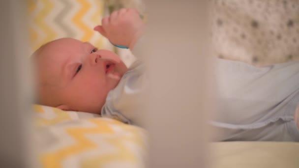 malé novorozeně leží v postýlce a okusuje hračku