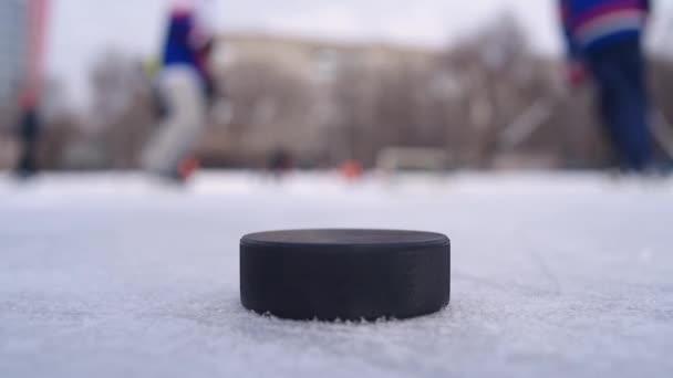 černý puk leží na ledě, kde muži hrají hokej v pozadí