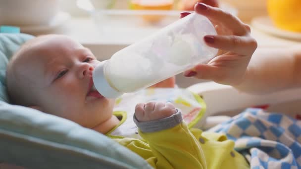 Mother feeds the baby from the bottle