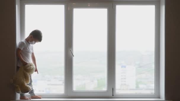malé dítě v masce sedí doma v karanténě a dívá se z okna na místo s plyšovým medvídkem. Prevence koronaviru a Covidu -19. Koncept