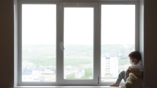 malý chlapec v masce sedí doma v karanténě a dívá se z okna na místo s plyšovým medvídkem. Prevence koronaviru a Covidu -19. Koncept