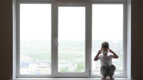 Malé dítě sedí doma v karanténě a snaží se nasadit lékařskou masku během koronaviru a Covid - 19 pandemie