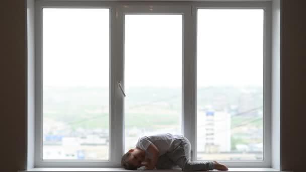 ein Kind in medizinischer Maske sitzt wegen Coronavirus und Covid -19 zu Hause in Quarantäne und schaut aus dem Fenster.