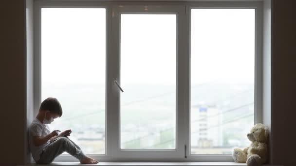 Malý chlapec sedí na okně s medvídkem v karanténě a hraje si v mobilním telefonu. Koronavirus a Covid Prevence - 19