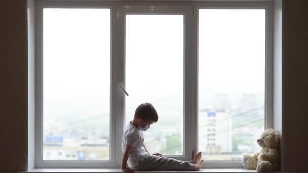 Malé dítě sedí doma s medvídkem v karanténě a hraje si na telefonu. Prevence koronaviru a Covidu - 19