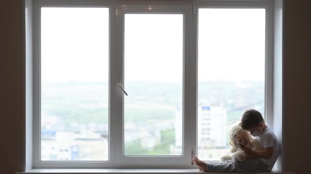 Malý chlapec sedí na okně s medvídkem v karanténě a hraje si v mobilním telefonu. Prevence koronaviru a Covidu - 19