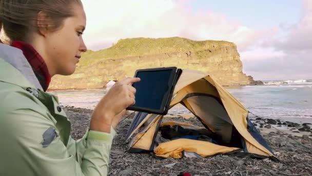 4 k orta tablet cihaz kullanarak ve Bankacılık uygulama yanındaki sarı  çadır kamp malzemeleri epik bir kamp maceraya kullanmak bağımsız gezgin  kadın