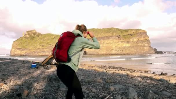 woman looking at ocean view with binoculars.
