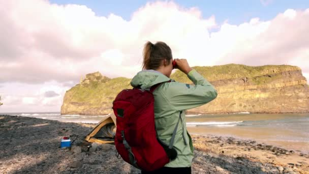4k medium of hiker, during leisure activities on holiday camping in yellow tent, young woman hiking and trekking and looking at ocean mountain view with binoculars.