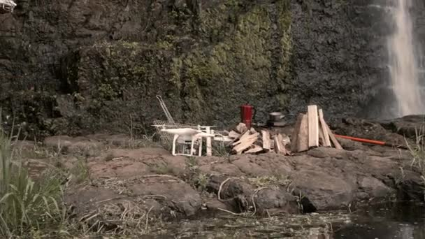 hiker flying drone in waterfall campsite