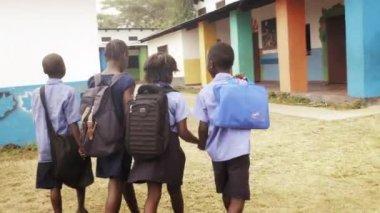 Group of African school children walking to school with backpacks.