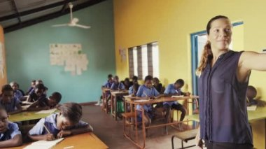 4k of side view of teacher explaining english alphabet off chalkboard.