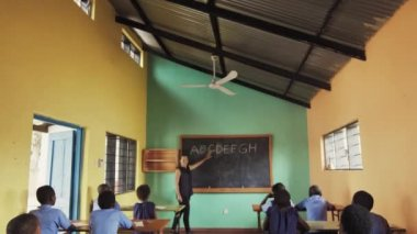 4k wide of classroom of African children learning english.