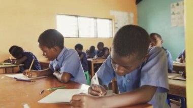 Classroom of African children writing English.
