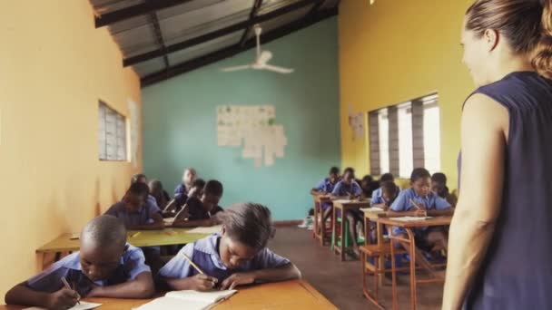 African students write english alphabet in notebooks.