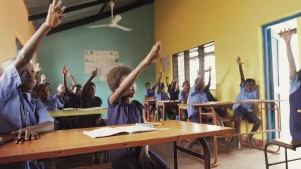 Front view of pupils raising hand in class to answer teachers question.