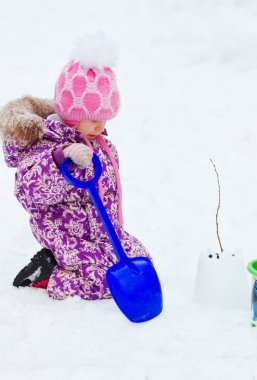 Cute little girl wearing bright colored snowsuit and pink hat playing with snow, shovel and building snow castle and decorating it in a cold winter day