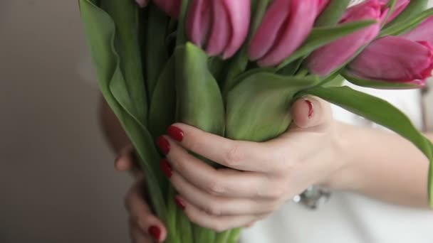 Young romantic woman with a bouquet of pink tulips