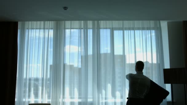 Businessman portrait silhouette getting dress - putting his jacket. the silhouette of a man wearing a suit. Silhouette of bearded groom standing in front of window