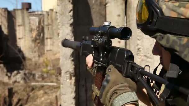 Soldat im Krieg mit Waffen. Junge Soldaten mit Gewehren, ein Soldat in Ausrüstung und mit Waffen inspiziert ein zerstörtes Haus außerhalb der Stadt.