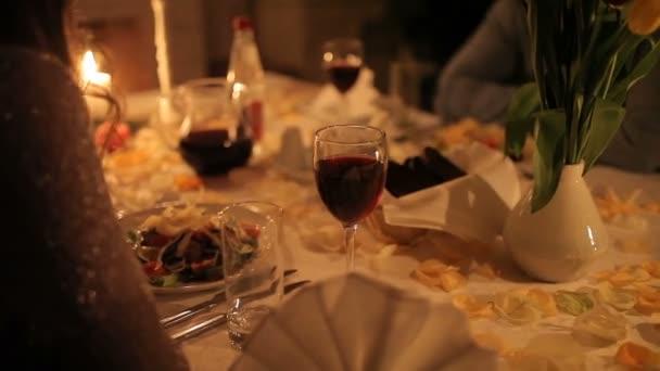 Ein Liebespaar speist bei Kerzenschein am Kamin. Nahaufnahme eines jungen Paares Händchen haltend während eines romantischen Abendessens bei Kerzenschein, Äpfel