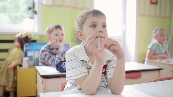 A fiú ceruzát tart a szájában, és ceruzával a szájában gondolkodik.