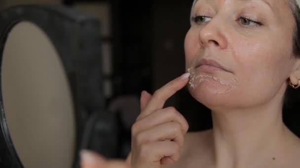 Žena si prohlíží oloupání obličeje v zrcadle. Exfoliovat starou kůži po oloupání.